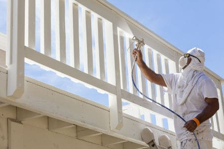 Spray Painting A Deck of A Home.